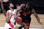 Oregon State forward Rodrigue Andela (34) blocks a shot by Houston forward Justin Gorham (4) during the first half of an Elite 8 game in the NCAA men's college basketball tournament at Lucas Oil Stadium, Monday, March 29, 2021, in Indianapolis. (AP Photo/Michael Conroy)