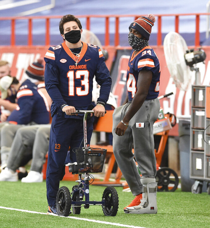 Injured Syracuse quarterback Tommy DeVito stands on the sideline with a knee scooter before an NCAA college football game against Liberty on Saturday, Oct 17, 2020, at the Carrier Dome in Syracuse, N.Y.  (Dennis Nett/The Post-Standard via AP)