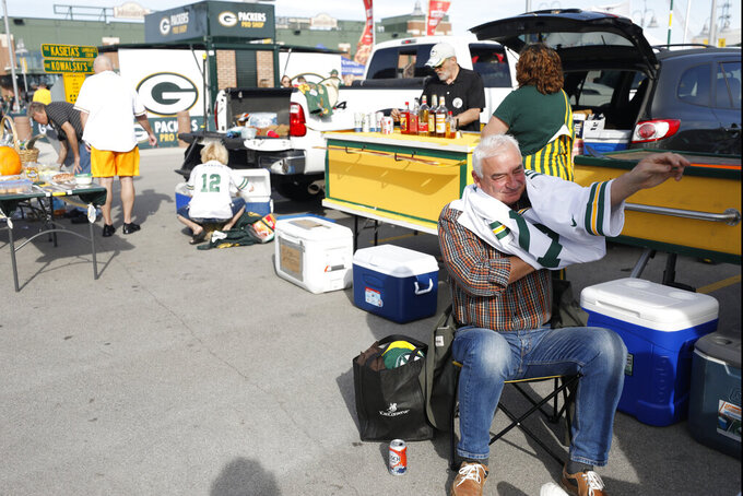 A Green Bay Packers fan puts on a jersey outside Lambeau Field before an NFL football game between the Packers and the Philadelphia Eagles, Thursday, Sept. 26, 2019, in Green Bay, Wis. (AP Photo/Jeffrey Phelps)