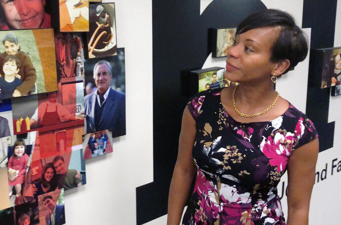 FILE - In this Aug. 15, 2019 file photo Kimberly Hall, director of the Ohio Department of Job and Family Services, looks over a photo display outside her office, in Columbus, Ohio. A federal lawsuit has been filed seeking to force Ohio to increase the amount of child support payments it provides to people who have taken custody of children they're related to. At issue in the complaint filed Thursday, Nov. 19, 2020 is a gap between payments to non-licensed relatives and relatives who become licensed. Hall, the director of Ohio's human services agency, told The Associated Press in October 2019 the agency planned to increase such payments.(AP Photo/Andrew Welsh-Huggins, File)