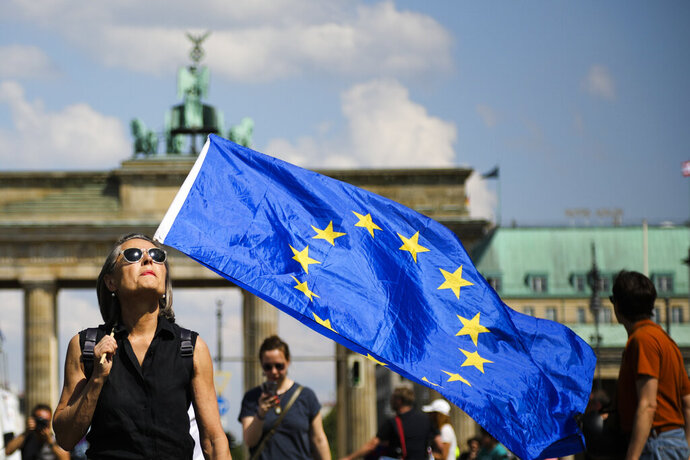 A woman holds a European flag as she attends a demonstration in Berlin, Germany, Sunday, May 19, 2019. People across Europe attend demonstrations under the slogan 'A Europe for All - Your Voice Against Nationalism'. (AP Photo/Markus Schreiber)