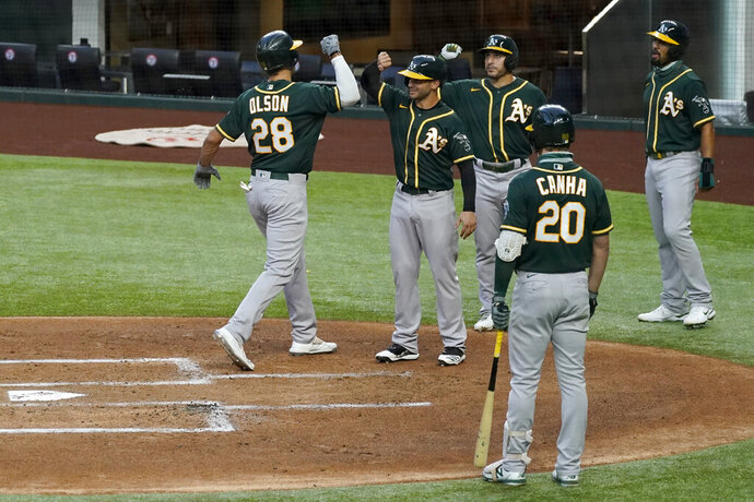 Oakland Athletics' Matt Olson (28) celebrates with Tommy La Stella, second from left rear, Ramon Laureano and Marcus Semien, right rear, as Mark Canha (20) looks watches after Olson hit a grand slam off Texas Rangers' Luis Garcia during the first inning of a baseball game in Arlington, Texas, Friday, Sept. 11, 2020. (AP Photo/Tony Gutierrez)