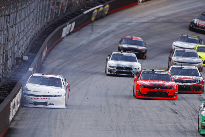 The car of Mason Diaz sits against the wall  as others pass during the NASCAR Xfinity Series auto race Friday, Aug. 16, 2019, in Bristol, Tenn. (AP Photo/Wade Payne)