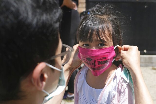 FILE - In this June 10, 2020, file photo, Olivia Chan's father helps her with a new mask she received during a graduation ceremony for her Pre-K class in front of Bradford School in Jersey City, N.J. School districts across America are in the midst of wrenching decisions during the summer about how to resume classes in settings radically altered by the coronavirus pandemic, with socially distanced school buses, virtual learning, outdoor classrooms and quarantine protocols for infected children as the new norm. (AP Photo/Seth Wenig, File)