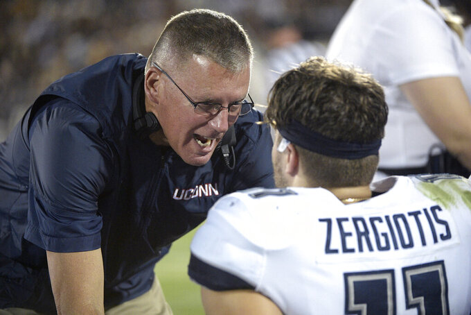 Connecticut head coach Randy Edsall, left, talks to quarterback Jack Zergiotis (11) on the bench during the first half of an NCAA college football game against Central Florida, Saturday, Sept. 28, 2019, in Orlando, Fla. (AP Photo/Phelan M. Ebenhack)