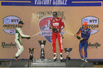 First place winner Marcus Ericsson, center, sprays champagne in celebration with third place finisher James Hinchcliffe, left, and second place finisher Scott Dixon in Victory Circle at the IndyCar Music City Grand Prix auto race Sunday, Aug. 8, 2021, in Nashville, Tenn. (AP Photo/Harrison McClary)