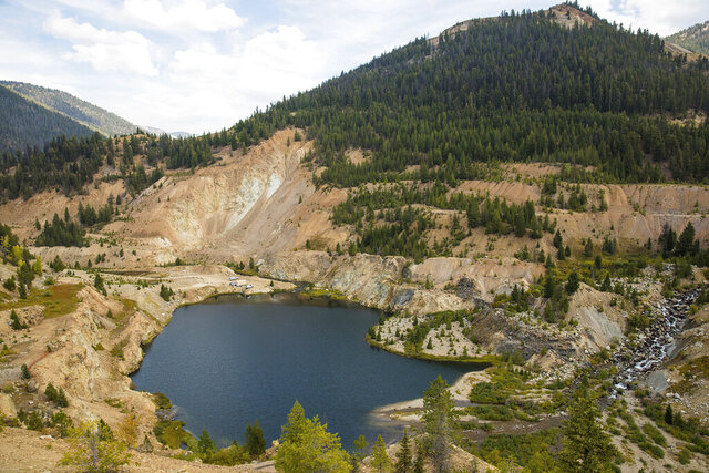 FILE - This Sept. 19, 2018, file photo, shows the Yellow Pine Pit open-pit gold mine in the Stibnite Mining District in central Idaho, where a company hopes to start mining again. A Canadian company that is seeking U.S. approval for three open-pit gold mines in central Idaho is suing the U.S. government contending U.S. officials are allowing water pollution at the heavily-mined site in violation of environmental laws. British Columbia-based Midas Gold filed the lawsuit Tuesday, Aug. 18, 2020, against the U.S. Forest Service under the citizen enforcement provision of the Clean Water Act. (Riley Bunch//The Idaho Press-Tribune via AP, File)