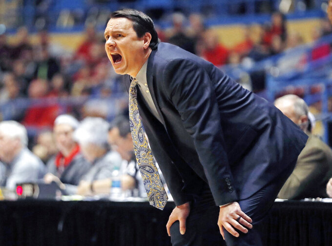 FILE - In this Dec. 15, 2018, file photo, Abilene Christian coach Joe Golding yells out at his players during the first half of an NCAA college basketball game against Texas Tech in Lubbock, Texas.  Golding hopes his team holds up better than his suit in the NCAA Tournament. He ripped his pants celebrating Abilene Christian's seeding Sunday night and wasn't able to get them repaired before leaving for Jacksonville, where the 15th-seeded Wildcats will face second-seeded Kentucky in the opening round Thursday. (AP Photo/Brad Tollefson, File)