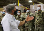 Texas Gov. Greg Abbott, foreground, addresses members of the National Guard during a visit to a Texas Division of Emergency Management Warehouse filled with Personal Protective Equipment, Tuesday, Aug. 4, 2020, in San Antonio. (AP Photo/Eric Gay)