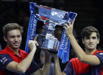 Pierre-Hugues Herbert of France, right, and Nicholas Mahut of France celebrate with the trophy as they pose for photographs after defeating Raven Klaasen of South Africa and Michael Venus of New Zealand following their ATP World Finals final doubles tennis match at the O2 arena in London, Sunday, Nov. 17, 2019. (AP Photo/Kirsty Wigglesworth)