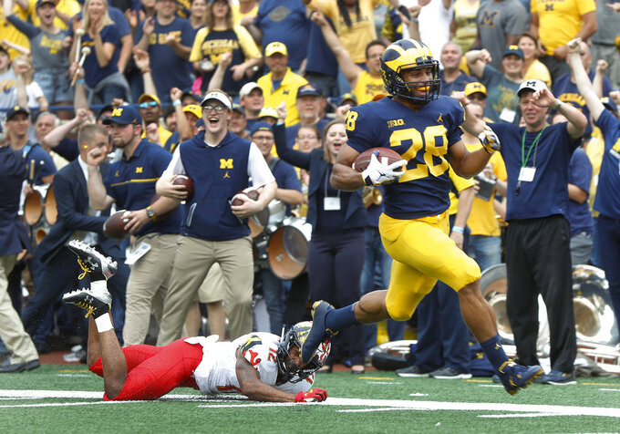 Michigan defensive back Brandon Watson (28) returns an interception  46-yards for a touchdown as Maryland wide receiver Taivon Jacobs (12) defends in the second half of an NCAA football game in Ann Arbor, Mich., Saturday, Oct. 6, 2018. (AP Photo/Paul Sancya)
