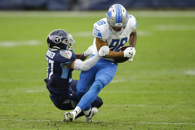 Detroit Lions tight end Hunter Bryant (86) is tackled by Tennessee Titans strong safety Amani Hooker during the first half of an NFL football game Sunday, Dec. 20, 2020, in Nashville, Tenn. (AP Photo/Ben Margot)