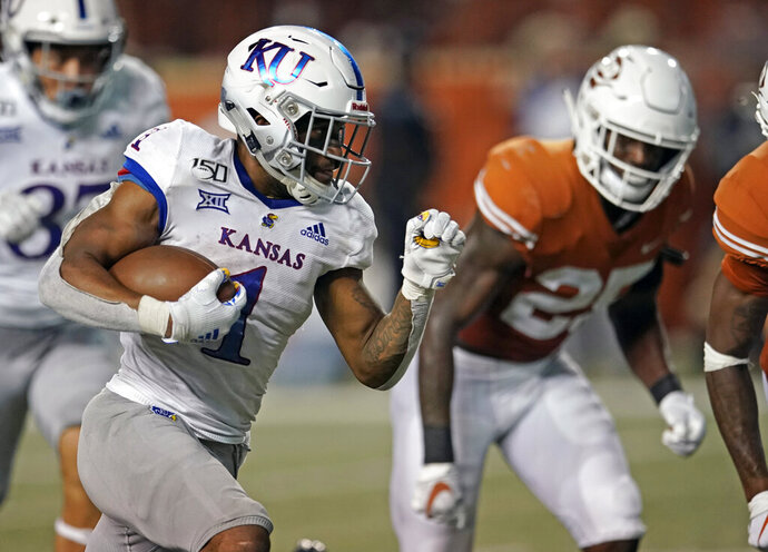 FILE - In this Oct. 19, 2019, file photo, Kansas' Pooka Williams Jr. (1) runs for a touchdown against Texas during the second half of an NCAA college football game in Austin, Texas. With some returning talent on both sides of the ball and continuity among his staff, Kansas coach Les Miles is confident that more progress will be made this season. (AP Photo/Chuck Burton, File)