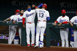 Texas Rangers' Elvis Andrus, center left, greets Joey Gallo (13) at the top of the dugout after Gallo hit a two-run home run in the sixth inning of a baseball game against the Los Angeles Angels in Arlington, Texas, Saturday, Aug. 8, 2020. (AP Photo/Tony Gutierrez)