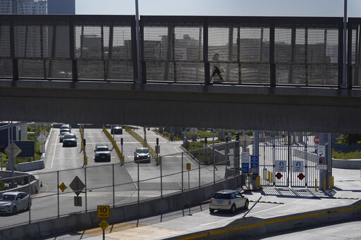 A few cars make their way north to cross into the United States from Tijuana, Mexico, Wednesday, Oct. 13, 2021, at the San Ysidro Port of Entry in San Diego. Beleaguered business owners and families separated by COVID-19 restrictions rejoiced Wednesday after the U.S. said it will reopen its land borders to nonessential travel next month, ending a 19-month freeze. (AP Photo/Gregory Bull)