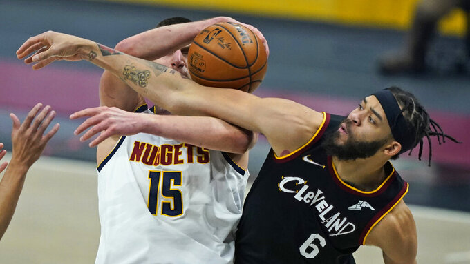 Cleveland Cavaliers' JaVale McGee (6) and Denver Nuggets' Nikola Jokic (15) vie for a rebound during the first half of an NBA basketball game Friday, Feb. 19, 2021, in Cleveland. (AP Photo/Tony Dejak)