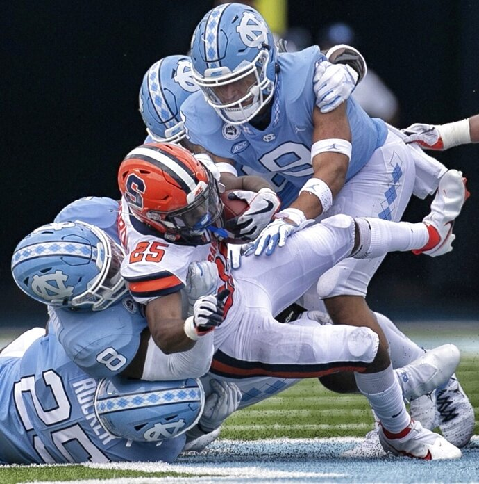 Syracuse running back Jawhar Jordan (25) is stopped by North Carolina's Kaimon Rucker (25), Khadry Jackson (8), and Cam'Ron Kelly (9) in the fourth quarter of an NCAA college football game Saturday, Sept. 12, 2020 in Chapel Hill, N.C. (Robert Willett/The News & Observer via AP, Pool)