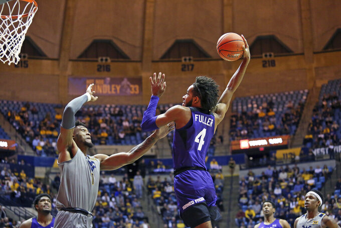 TCU guard PJ Fuller (4) shoots as West Virginia forward Derek Culver (1) defends during the first half of an NCAA college basketball game Tuesday, Jan. 14, 2020, in Morgantown, W.Va. (AP Photo/Kathleen Batten)
