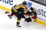 Boston Bruins' Matt Grzelcyk (48) checks New Jersey Devils' Nico Hischier (13) during the second period of an NHL hockey game in Boston, Saturday, Oct. 12, 2019. (AP Photo/Michael Dwyer)