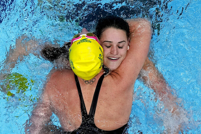 Kaylee McKeown, of Australia, is congratulated by teammate Emily Seebohm after winning the final of the women's 100-meter backstroke at the 2020 Summer Olympics, Tuesday, July 27, 2021, in Tokyo, Japan. (AP Photo/Morry Gash)