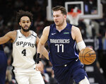 Dallas Mavericks guard Luka Doncic (77) drives around San Antonio Spurs guard Derrick White (4) during the first half of an NBA basketball game in San Antonio, Tuesday, March 10, 2020. (AP Photo/Eric Gay)