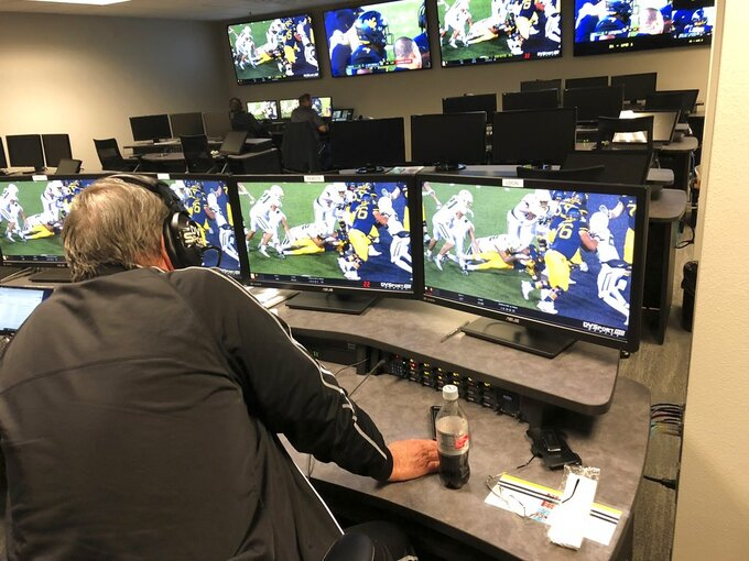 David Warden, the Big 12's replay coordinator, takes a close look at a play that was initially ruled a touchdown for West Virginia running back Leddie Brown during an NCAA college football game against Baylor, in the conference's centralized replay center in Irving, Texas, Thursday, Oct. 25, 2018. The call was overturned, and the ball placed on the 1-yard line. (AP Photo/Stephen Hawkins)