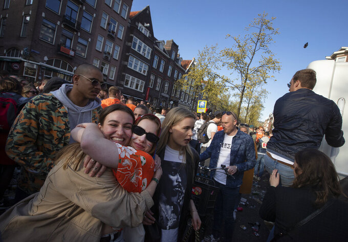 A man climbs on a camper, right, as an empty beer bottle, top right, is thrown at the vehicle as it passes through a crowd of people celebrating King's Day in the center of Amsterdam, Netherlands, Tuesday, April 27, 2021. Crowds have gathered in cities across the Netherlands despite authorities urging people to stick to coronavirus social distancing regulations as the country marks King Willem-Alexander's birthday, a national holiday. (AP Photo/Peter Dejong)