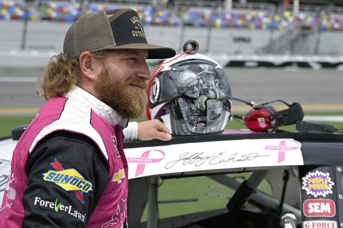 Jeffrey Earnhardt stands next to his car and his helmet, bearing the likeness of his grandfather Dale Earnhardt, before the restart of a NASCAR Xfinity Series auto race at Daytona International Speedway, Saturday, Aug. 28, 2021, in Daytona Beach, Fla. (AP Photo/Phelan M. Ebenhack)