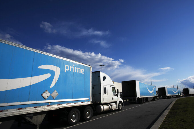 FILE - This April 21, 2020 file photo shows Amazon tractor trailers line up outside the Amazon Fulfillment Center in the Staten Island borough of New York.  Amazon said Wednesday, June 2, 2021,  that it will hold its annual Prime Day over two days in June this year, the earliest it has ever held the sales event.  (AP Photo/Mark Lennihan, File)