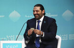 Lebanese Prime Minister Saad Hariri reacts after receiving a $100 bill from a moderator who said he could keep it if he sold him on investing in Lebanon during the World Government Summit in Dubai, United Arab Emirates, Sunday, Feb. 10, 2019. At the summit on Sunday, Hariri urged investment in Lebanon as it faces an economic crisis that has seen thousands of people laid off and one of the highest public debts in the world. (AP Photo/Jon Gambrell)