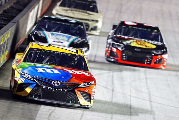 Kyle Busch (18) leads the field down the back straight during the NASCAR Cup Series auto race Saturday, Aug. 17, 2019, in Bristol, Tenn. (AP Photo/Wade Payne)