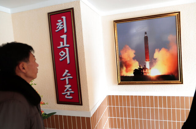 In this Nov. 26, 2019, photo, a man looks at a photo of the launch of a missile hanging on the wall of a factory workers' dormitory in Pyongyang, North Korea. Fears rise that North Korea's year-end deadline to the U.S. to offer some new initiative to the nuclear-standoff means that nearly two years of head-spinning diplomatic engagement might be in danger of falling apart. Sign in Korean reads;