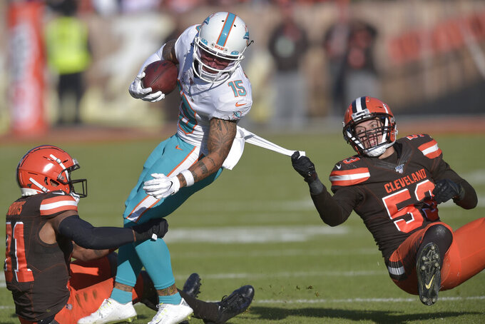 Miami Dolphins wide receiver Albert Wilson (15) tackled by Cleveland Browns safety Juston Burris (31) and middle linebacker Joe Schobert (53) during the first half of an NFL football game, Sunday, Nov. 24, 2019, in Cleveland. (AP Photo/David Richard)