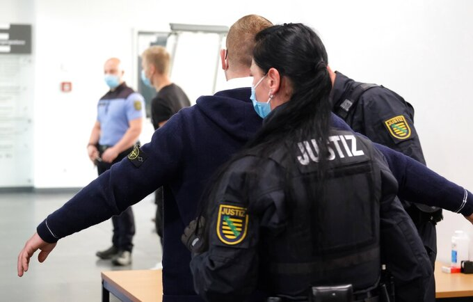 Kevin A. right, second name not given, defendant in a trial for an attack on a Jewish restaurant three years ago is searched, prior to his trial, at a court in Chemnitz, Germany, Wednesday, Sept. 8, 2021. A 30-year-old man went on trial Wednesday for an attack on a Jewish restaurant three years ago in the eastern German city of Chemnitz in which the owner was injured and the restaurant damaged. Prosecutors allege that the man, whose name was not given in line with German privacy rules, was motivated by far-right ideology. He has been indicted on charges of severe aggravated assault and property damage. (Sebastian Willnow/dpa via AP)