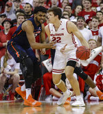 Illinois' Adonis De La Rosa, left, reaches in on Wisconsin's Ethan Happ, right, during the first half of an NCAA college basketball game Monday, Feb. 18, 2019, in Madison, Wis. (AP Photo/Andy Manis)