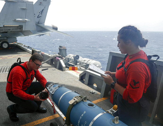 In this Wednesday, May 15, 2019, photo released by the U.S. Navy, Aviation Ordnanceman 3rd Class Alexandrina Ross, right, and Aviation Ordnanceman Airman Hunter Musil, left, inspect a bomb on the USS Abraham Lincoln while it sails in the Arabian Sea. U.S. diplomats warned Saturday, May 18, 2019, that commercial airliners flying over the wider Persian Gulf faced a risk of being