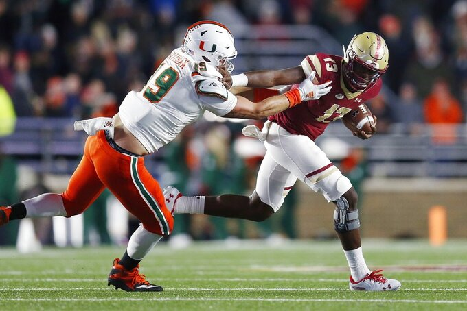 Boston College quarterback Anthony Brown (13) carries the ball against Miami defensive lineman Scott Patchan (19) during the first half of an NCAA college football game in Boston, Friday, Oct. 26, 2018. (AP Photo/Michael Dwyer)