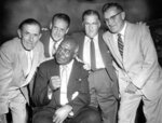 """Judge Fred W. """"Duke"""" Slater, seated, of University of Iowa's undefeated football team of 1921, huddles with former teammates at a luncheon honoring him on Aug, 13, 1958, at the Sherman Hotel in Chicago. Other players are, from left, Aubrey Devine, Les Belding, Bill Kelly and Glen Devine. (Chicago Tribune via AP)"""