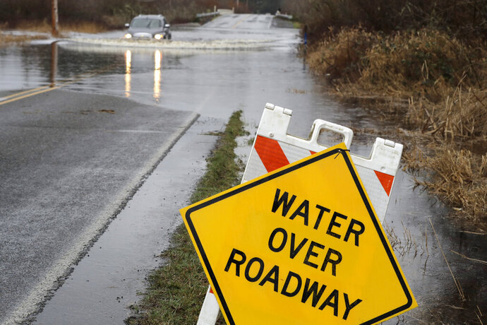 A man drives through a flooded roadway, Tuesday, Jan. 7, 2020, near Littlerock, Wash. A storm that has brought record rainfall to the Northwest has prompted flood warnings, disrupted train traffic, closed roads and caused some power outages. (AP Photo/Ted S. Warren)
