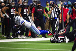 Dallas Cowboys running back Ezekiel Elliott gets tripped up by an Atlanta Falcons defender Sunday, Sept. 20, 2020, in Arlington, Texas. (Yffy Yossifor/Star-Telegram via AP)