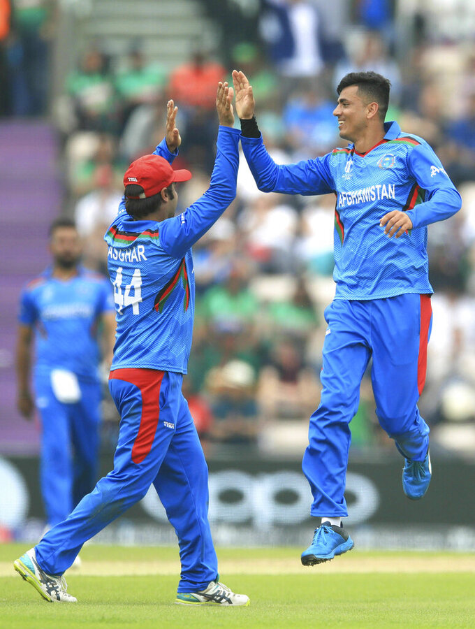 Afghanistan's Mujeeb Ur Rahman, right, celebrates taking the wicket of Bangladesh's Soumya Sarkar during the Cricket World Cup group stage match at The Hampshire Bowl, Southampton, England, Monday June 24, 2019. (Adam Davy/PA via AP)
