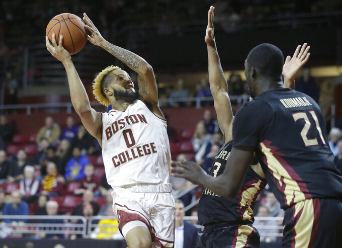 Boston College's Ky Bowman looks for an opening past Florida State's Christ Koumadje (21) in the second half of an NCAA college basketball game, Sunday, Jan. 20, 2019, in Boston. (AP Photo/Steven Senne)