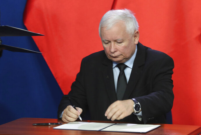 The leader of the Polish ruling party, Jaroslaw Kaczynski,signs the coalition document in Warsaw, Poland, Saturday, Sept. 26, 2020. The three parties in Poland's conservative coalition government signed a new coalition agreement on Saturday, putting aside disagreements. But they gave no details, leaving lingering uncertainty about how the Cabinet will look in practice after an expected reshuffle.(AP Photo/Czarek Sokolowski)