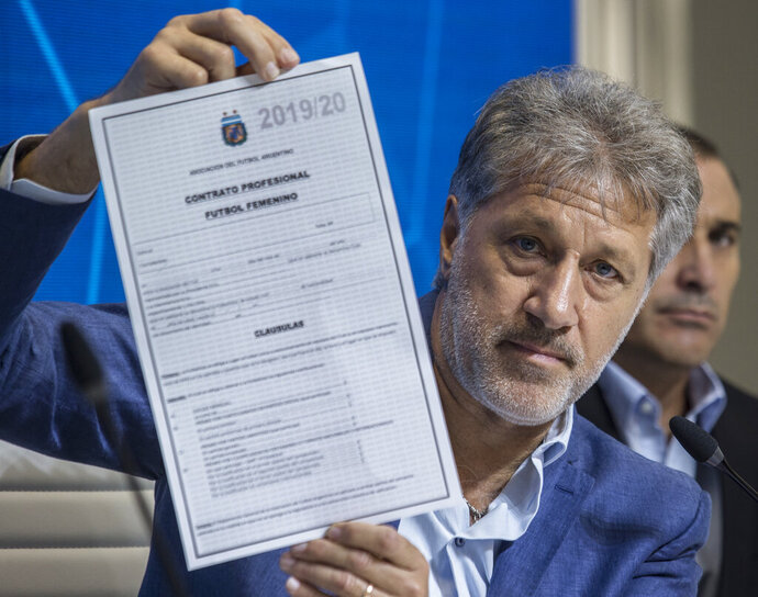 General Secretary of the Argentina's Footballers' Union (FAA) Sergio Marchi holds up the contract to implement a plan to professionalize women's soccer during a preseason conference in Buenos Aires, Argentina, Saturday, March 16, 2019. Almost 90 years after men's soccer turned professional in Argentina, the women's game is still being played by amateur athletes who get little to no money for their work on the field. (AP Photo/Daniel Jayo)