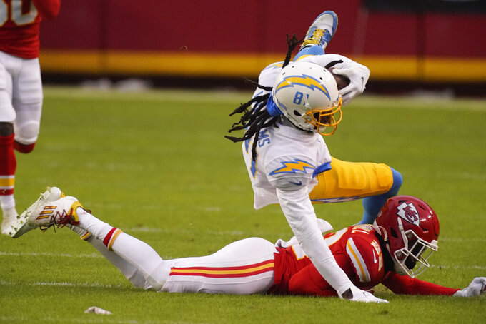 Los Angeles Chargers wide receiver Mike Williams, top, is tackled by Kansas City Chiefs safety Juan Thornhill after catching a pass during the first half of an NFL football game, Sunday, Jan. 3, 2021, in Kansas City. (AP Photo/Charlie Riedel)