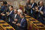 Greek Prime Minister kyriakos Mitsotakis, front, applauds with other members of the government during a parliamentary session to vote for the new Greek President, in Athens, on Wednesday, Jan. 22, 2019. High court judge Katerina Sakellaropoulou has been elected at Greece's first female president with an overwhelming majority in a parliamentary vote. (AP Photo/Petros Giannakouris)