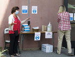 Election worker Martha Swasey, left, greets a voter at Hopkinton Middle-High School in Hopkinton, N.H., on Tuesday, Sept. 8, 2020. Voters choosing nominees for governor, U.S. Senate, Congress and other races faced numerous changes and safeguards implemented to prevent spread of the coronavirus. (AP Photo/Holly Ramer)