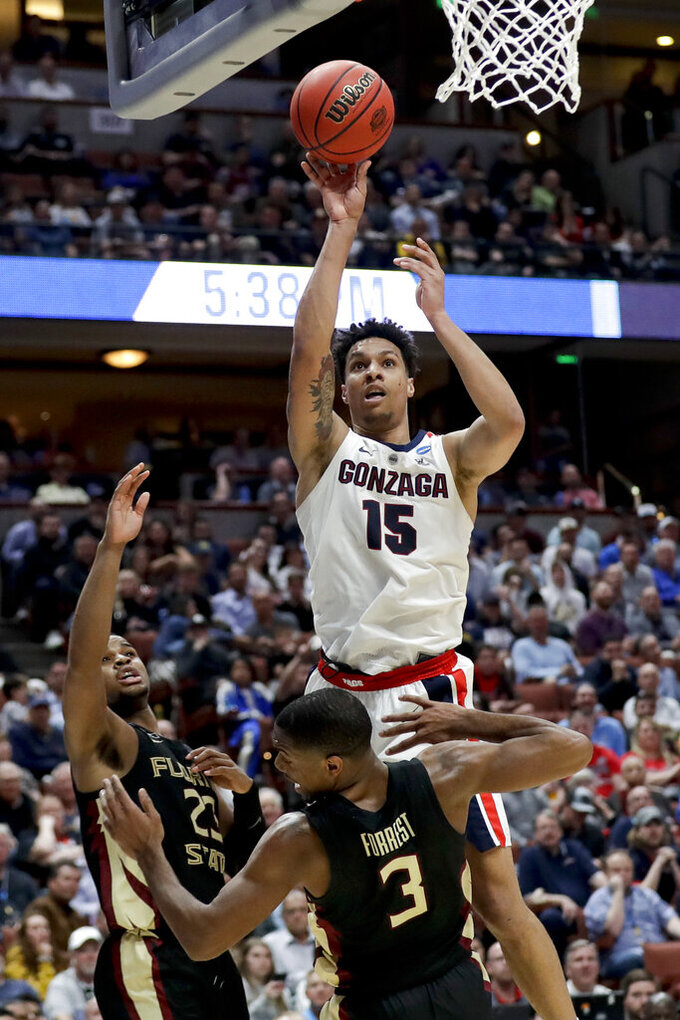 Gonzaga forward Brandon Clarke, top, shoots over Florida State guard M.J. Walker, left, and guard Trent Forrest during the second half an NCAA men's college basketball tournament West Region semifinal Thursday, March 28, 2019, in Anaheim, Calif. (AP Photo/Marcio Jose Sanchez)