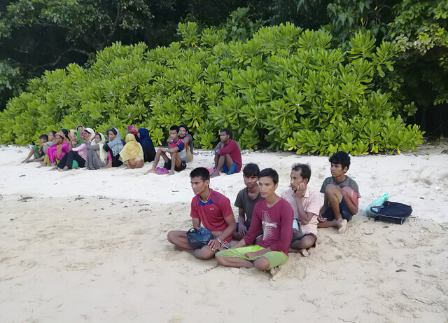 In this photo taken Sunday, July 26, 2020, by the Malaysian Maritime Enforcement Agency, shows rescued Rohingya refugees on a beach on Rebak Island off the resort island of Langkawi, Malaysia. Malaysian authorities say 26 Rohingya refugees, who were feared to have drowned after jumping off their boat off the northern resort island of Langkawi, have been located alive hiding on an islet nearby. (Malaysian Maritime Enforcement Agency via AP)