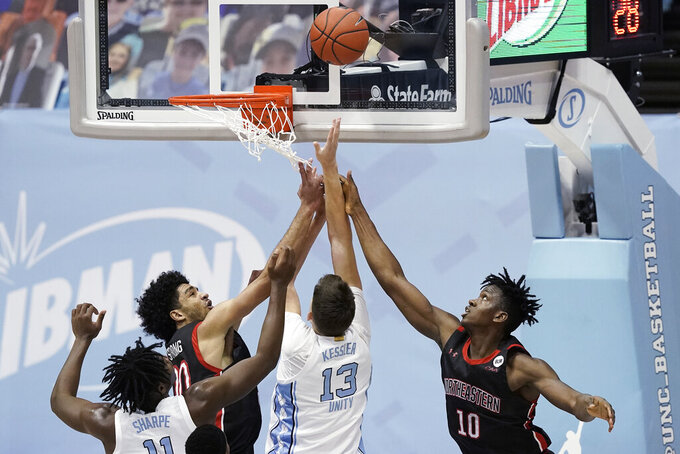 Northeastern forwards Jason Strong (00) and Greg Eboigbodin (10) defend against North Carolina forward Walker Kessler (13) during the second half of an NCAA college basketball game in Chapel Hill, N.C., Wednesday, Feb. 17, 2021. (AP Photo/Gerry Broome)